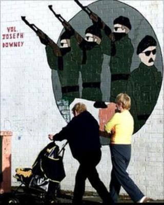 Two women pushing pram past paramilitary mural