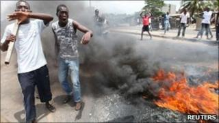 Anti-Gbagbo protesters stand near a roadblock and burning tyres in the Abobo area of Abidjan 3 March 2011