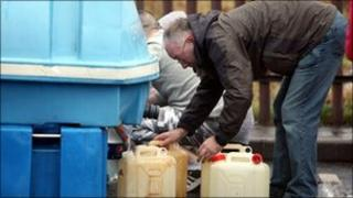 Man filling water cans from tank