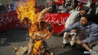Fuel price protesters burn an effigy depicting the International Monetary Fund and World Bank in Karachi