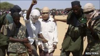 Al-Shabab members stand looking down on a body of an AU peacekeeper (not seen) on 24 February 2011