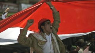 Backdropped by a Yemeni flag, an anti-government protestor shouts slogans during a demonstration demanding the resignation of the Yemeni President in Sanaa (5 March)