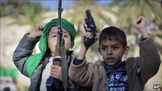 Children of a pro-Gaddafi soldier wave his guns at a rally in Green Square, Tripoli, 6 March