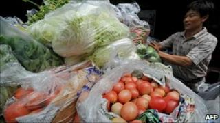 A vendor sells vegetables at a stall in Bangkok