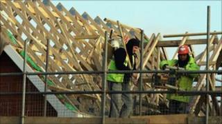Builders near the roof of a house
