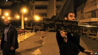 Protester with the sign of the state security building in Nasr City, Cairo, 5 March