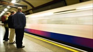 Commuters wait for a Tube train