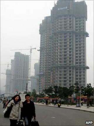 Pedestrians pass a property construction site in Chongqing