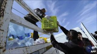 A man supplies water to refugees who fled Libya at a refugee camp at the international Airport of Djerba