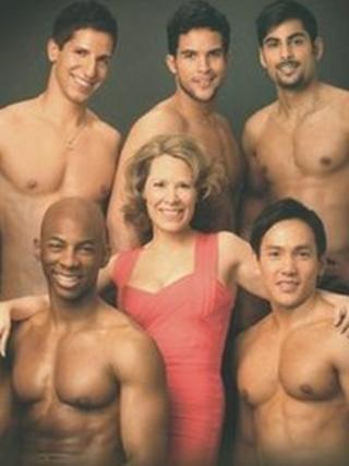JC Davies surrounded by topless men