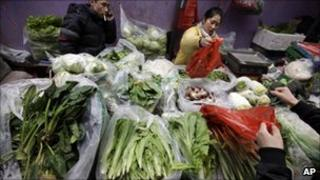 Vendors sell vegetables at a market in China