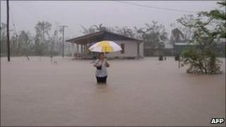 """March 8, 2011 woman in floodwater during heavy rain in Cardwell, in the far north of Australia""""s Queensland."""