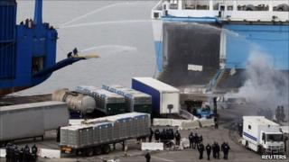 Strikers spray riot police with hoses in the port of Marseille, 10 March