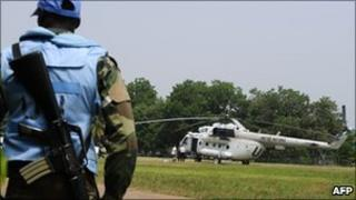 An UN peacekeeper in Ivory Coast stands guard by an UN helicopter - January 2011