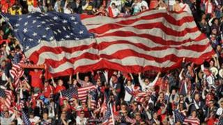 American football fans holding a huge American flag