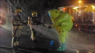 Firefighters hosing down a crew member in a gas-tight suit