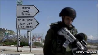 An Israeli soldier guards a road junction near Itamar in the West Bank - 12 March 2011