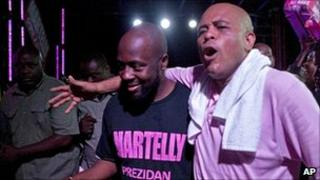 Haitian presidential candidate and Haitian born singer Wyclef Jean arm-in-arm at a campaign rally, 11 March