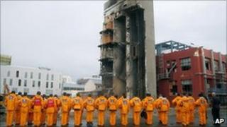 Japan Disaster Relief Team observes a moment of silence near at the collapsed CTV building in Christchurch, New Zealand, Sunday, March 6, 2011