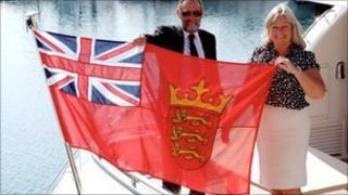 """Registrar Piers Baker and Assistant Registrar Debbie Podger with Jersey's """"defaced"""" Red Ensign"""