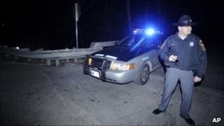 A Virginia state trooper stands by his patrol vehicle