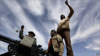 Anti-government rebels stand on their vehicle shouting slogans against Col Gaddafi at a desert road between Agela and Ras Lanuf, eastern Libya, on 12 March 2011.