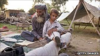 Man and boy in camp after Pakistan flooding