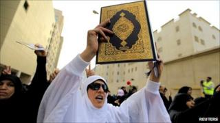 An anti-government protester holds a copy of the Koran as she passes by the Saudi Embassy in Manama, 15 March 2011