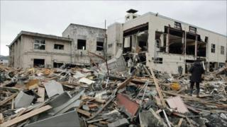 A resident stands on rubble in Ozuchi, Iwate prefecture, on 15 March