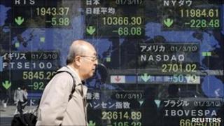 Man walking past stock board in Tokyo