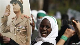 A schoolgirl shows her loyalty to Col Gaddafi during a demonstration outside a hotel where foreign media are staying in Tripoli on Monday