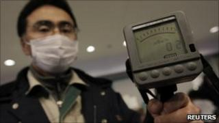 An employee of Yamagata city office holds a Geiger counter to detect radiation