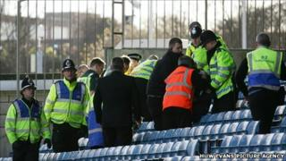 Police and paramedics attend to the injured fan at the Millwall ground