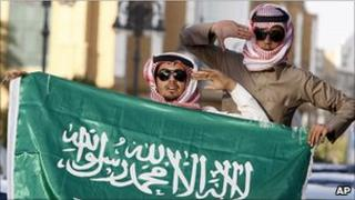 Saudis wave the Saudi national flag after Saudi King Abdullah announced his stimulus package