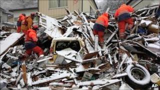 Firemen picking through collapsed wreckage