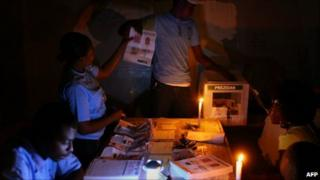 Election workers count ballots in Haiti by candlelight