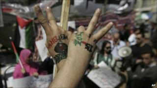 A Palestinian protester flashes the victory sign during a demonstration calling for unity between the rival Palestinian factions of Fatah and Hamas in the West Bank town of Ramallah