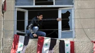 A Syrian security man, sets Syrian flags through a broken window of an office destroyed by Syrian anti-government protesters, in the southern city of Daraa, Syria
