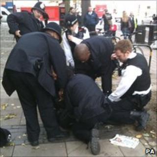 Police restrain John Russell Flint outside Highbury Corner Magistrates' Court