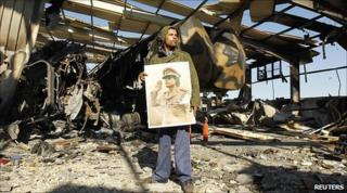 Pro-Gaddafi supporter in ruins of bombed-out building inTripoli. 22 March 2011