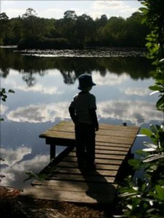 Silhouette of a child standing on a jetty
