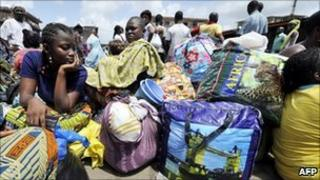 People wait to board buses at the Adjame bus station in Abidjan (22 March 2011)