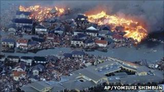 Flaming houses surrounded by debris and water following a tsunami, Natori city