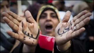 """A Libyan woman reacts with her hands written on them in Arabic """" I love Libya"""""""