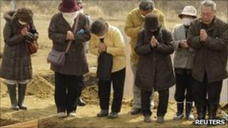 Mourners at a temporary mass grave in Miyagi prefecture, northern Japan, 25 March 2011