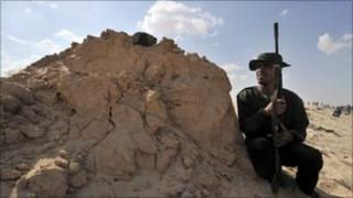 Libyan rebel takes cover as they try to retake the town of Ajdabiya