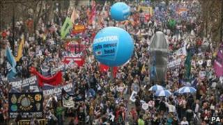 Demonstrators assemble near Waterloo Bridge before the start of the anti-cuts march, 26 March 2011