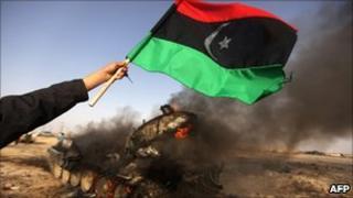 Libyan rebel holds a national flag beside a burning Gaddafi tank