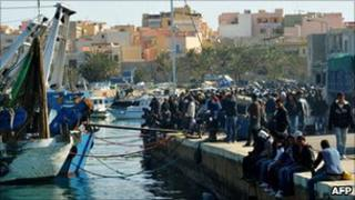North African migrants wait at the port in Lampedusa, Italy (27 March 2011)