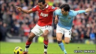 Manchester United's midfielder Nani (L) tussles with Manchester City's midfielder David Silva (R)